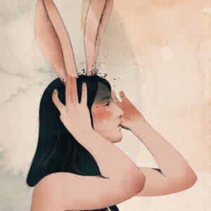ragazza nuda che tiene la testa con le mani e orecchie lunghe da coniglio